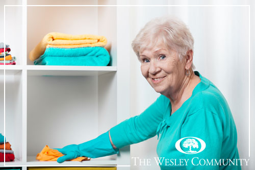Smiling senior woman cleaning house