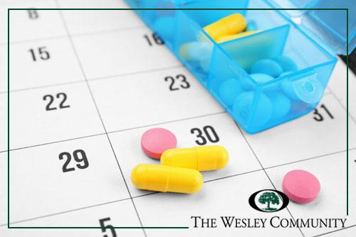 Pills and a pill box on top of a calendar.