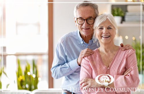 A happy senior couple standing together in a kitchen.