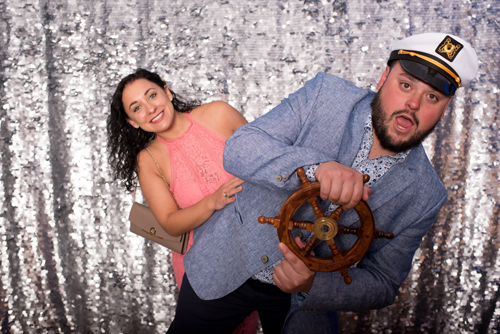couple posing for photo with ship wheel