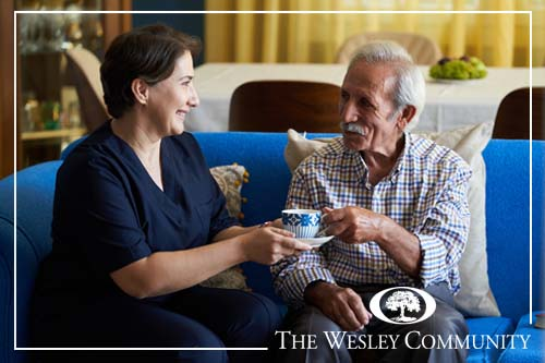 Professional helpful caregiver at nursing home. Health visitor and a senior man during home visit. Young caregiver in uniform and elderly man drinking tea