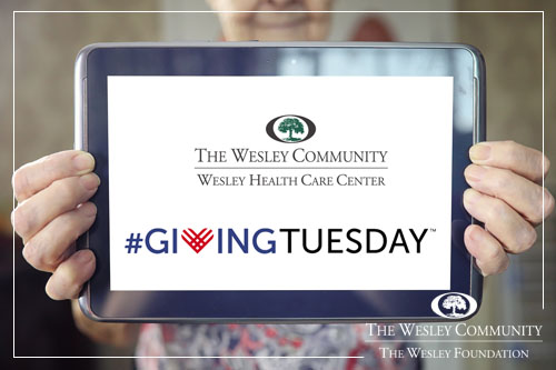 elder woman holding tablet with the #GivingTuesday and Wesley Health Care Center logos on the screen.