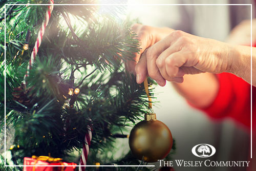christmas tree with senior hands hanging an ornament