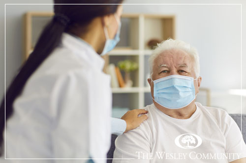 A masked home care aide assisting senior man in a mask.