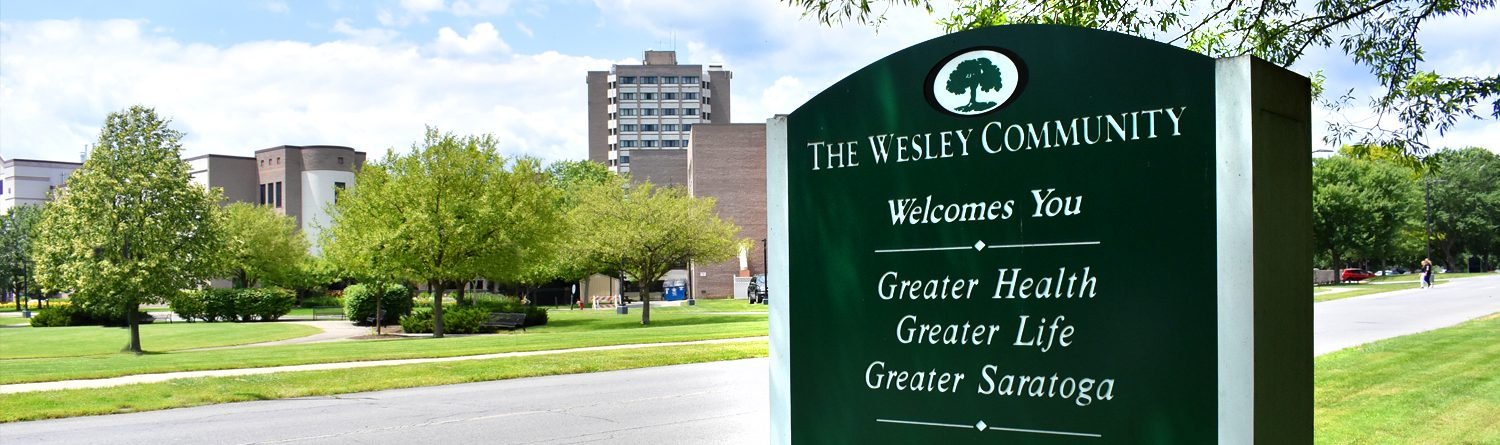 The Wesley entrance sign in the foreground with Wesley Health Care Center in the background.