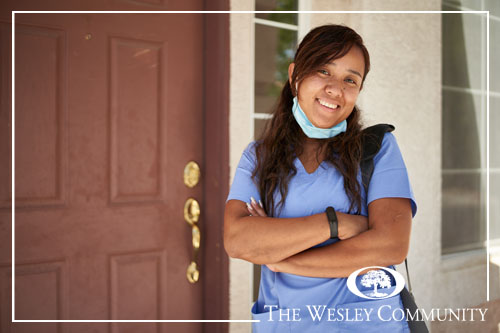 A happy nurse in front of her house.