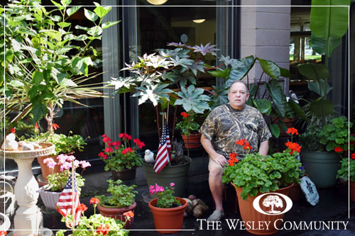 A man sitting among a large number of potted plants.