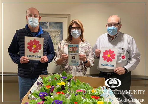 THree people in surgical masks standing before a cart of primrose plants.
