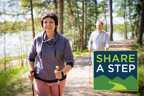 A happy woman and man walking on a path with hiking poles.