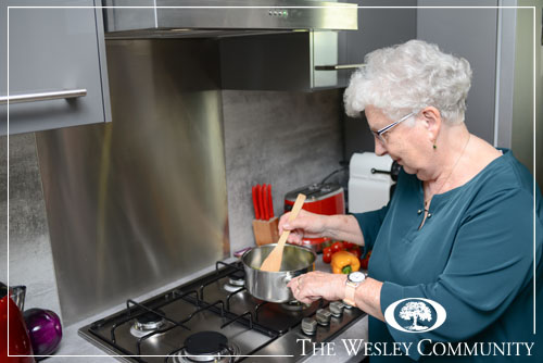 Happy senior active woman cooking at home in a modern kitchen.