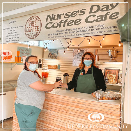 A woman handing a nurse a cup of to-go coffee.
