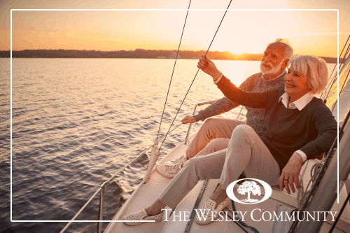 A senior couple enjoing a sunset from a sailboat.