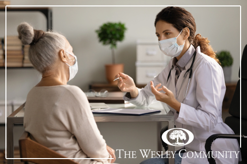 A senior woman speaking with a doctor.