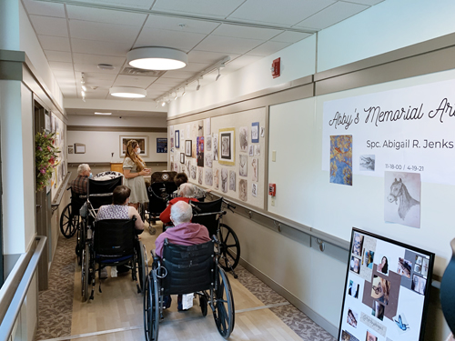 A woman presenting artwork to a group of nursing home residents.